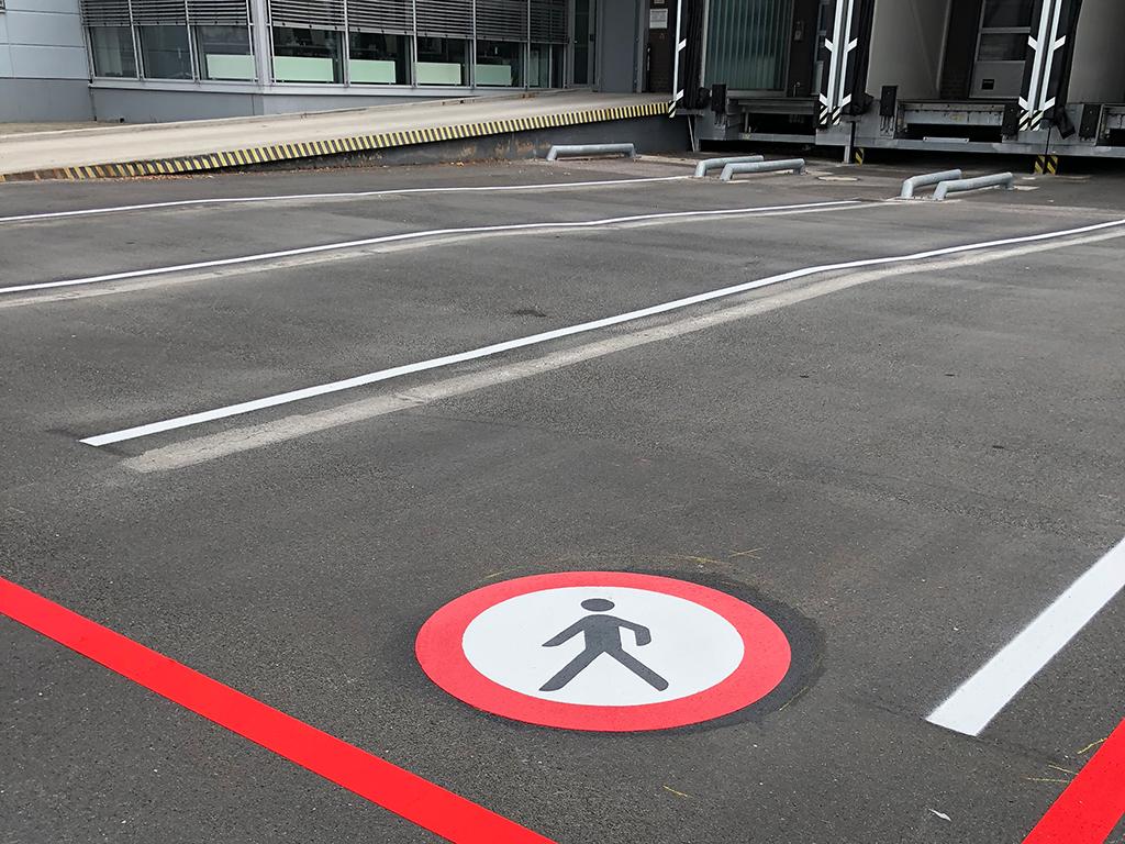 Gefahrenzone: Kennzeichnen eines Verbots für Fußgänger mittels Thermoplastik in einer Ladezone