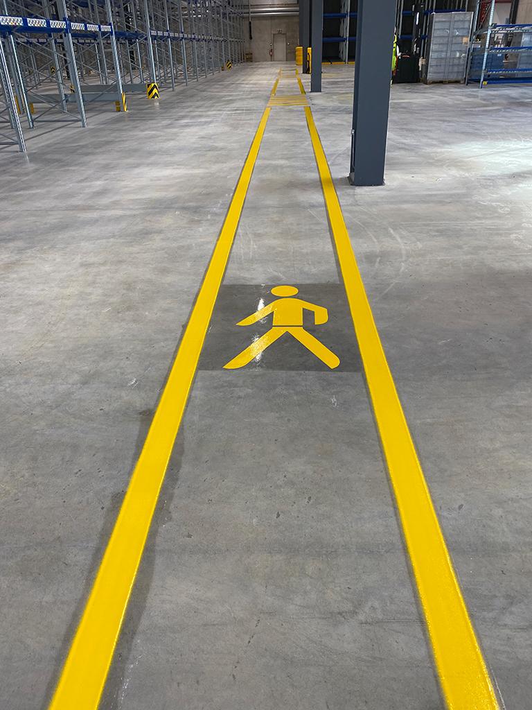 Markierung eines Gehwegs in einer Industriehalle